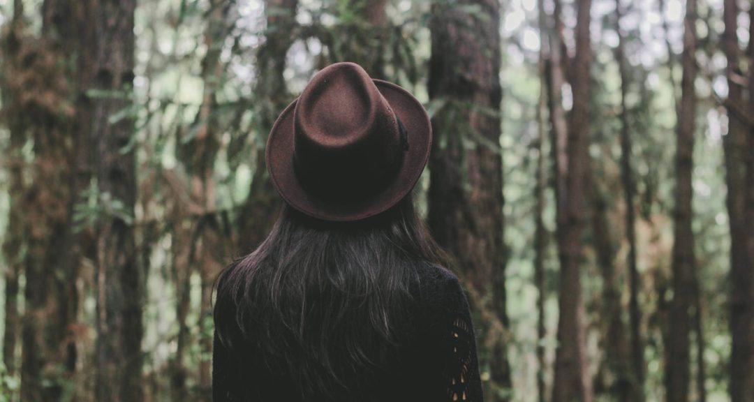 brunette in hat in woods